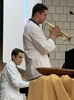 man in a white lab coat standing and playing a trumpet while another man in a white lab coat plays the piano