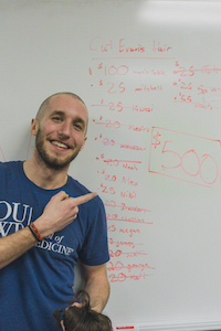 man in a blue O U W B t-shirt pointing to writing on a white board