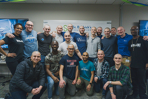 group of men with shaved heads in front of a St. Baldrick's poster