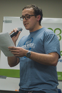 man in a blue shirt speaking into a microphone, holding a sheet of paper