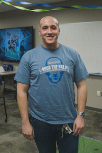 man with a shaved head in a blue t-shirt that says Rock the Bald, smiling at the camera