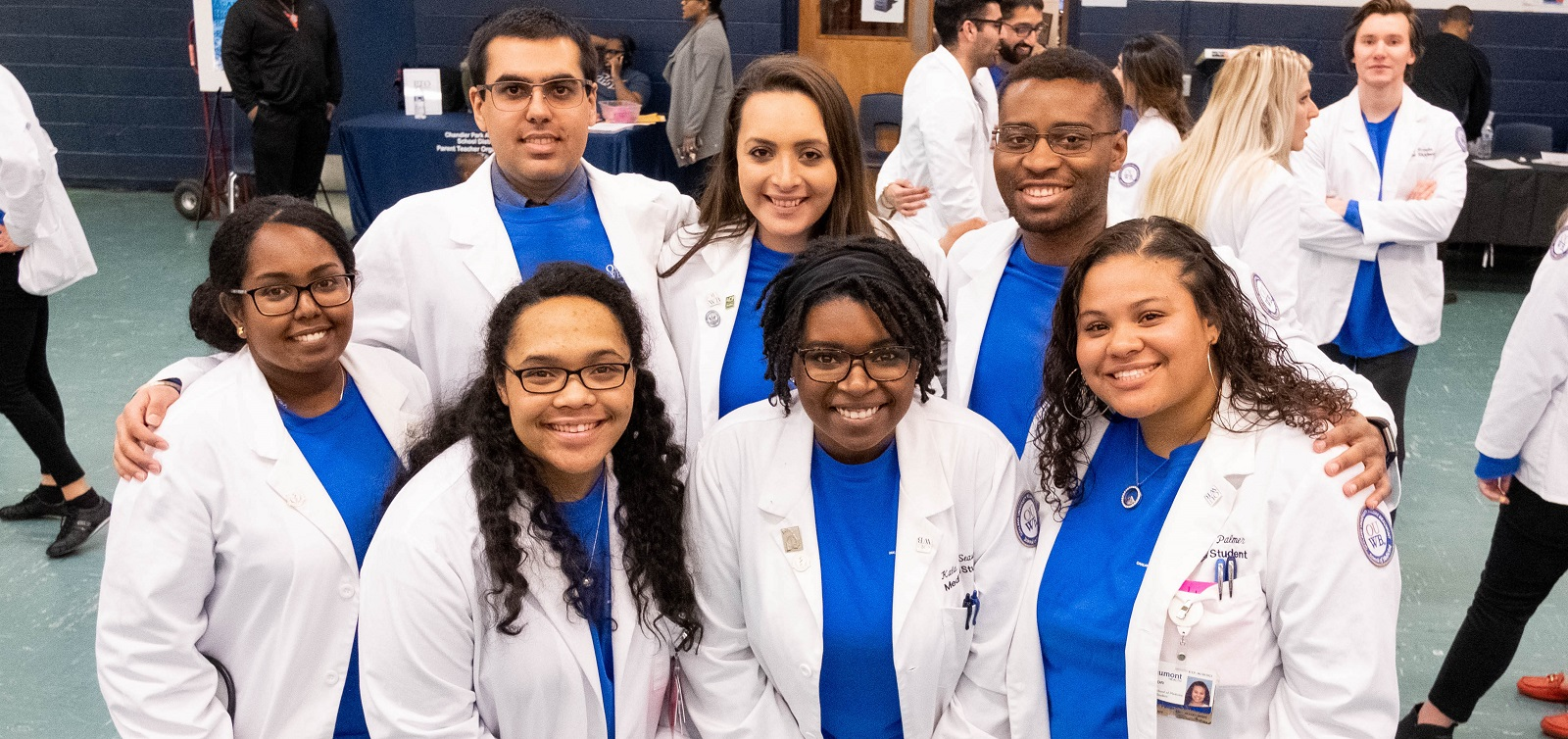 A group of med students wearing their white coats smiles in a group. They are volunteering at the annual Chandler Park Health Fair and Taste Test.