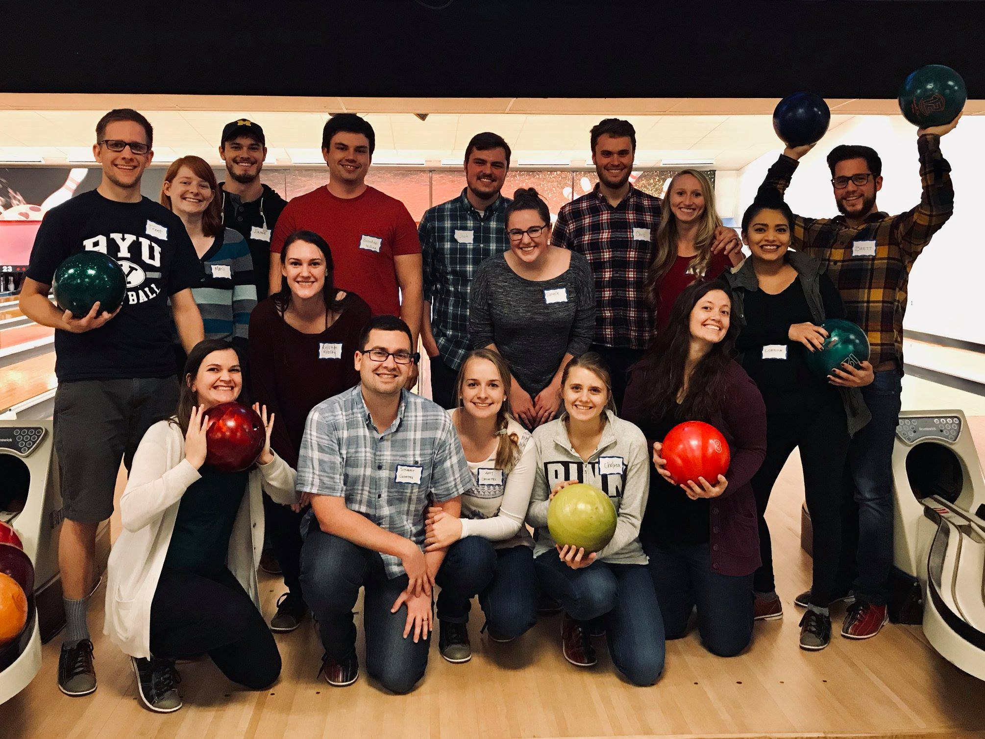 A group of OUWB students and their significant others pose with their bowling balls at the bowling alley.