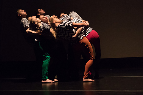 dance company members in a cluster leaning back into each other wearing bright pants and black and white shirts