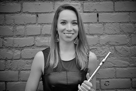 Amanda Blaikie holding a flute in front of a brick wall