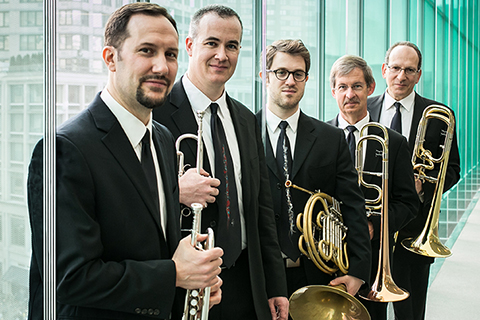 Five male members of the American Brass Quintet wearing black suits holding brass instruments
