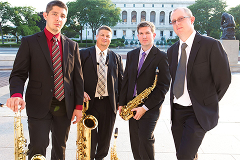 members of the Assembly Saxophone Quartet in suits, holding saxophones