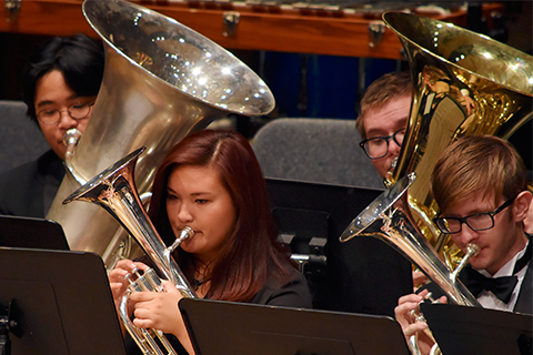 four members of the brass ensemble playing brass instruments