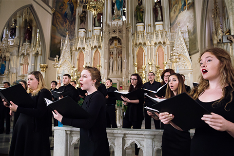 Chorus Chorale dressed in black, singing in an ornate church