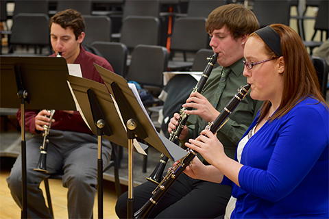 three students seated, playing clarinet
