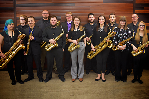 A group of students standing, holding saxophones