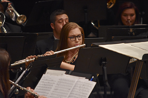 woman playing the flute as part of the Oakland University Wind Symphony