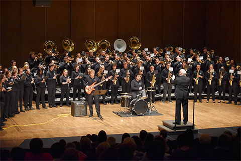Large band dressed in black performing on a stage in front of an audience