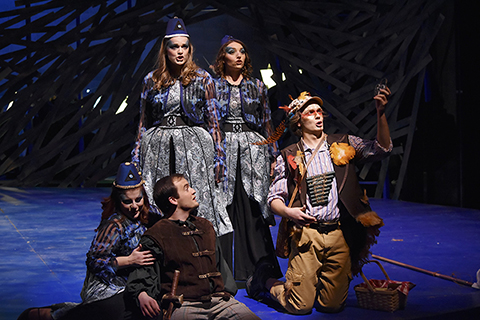 Performers in Martha in royal and peasant costumes on stage with blue lighting