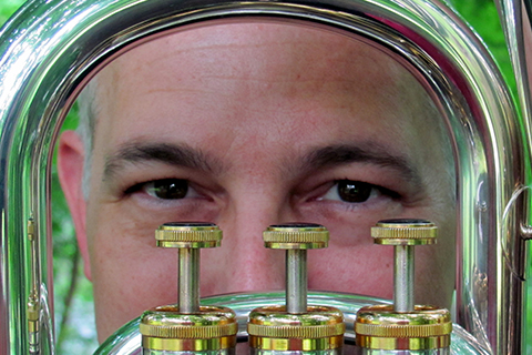 Close up of Kenneth Kroesche's face framed by a brass instrument with 3 keys