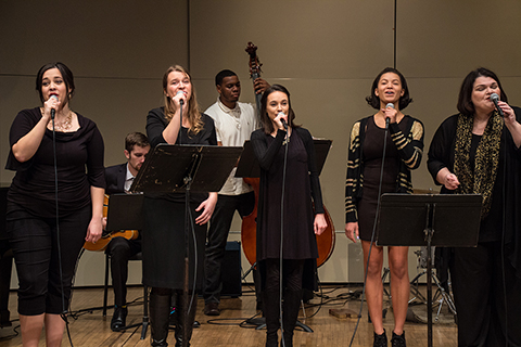 five female jazz singers with microphones standing in front of musicians