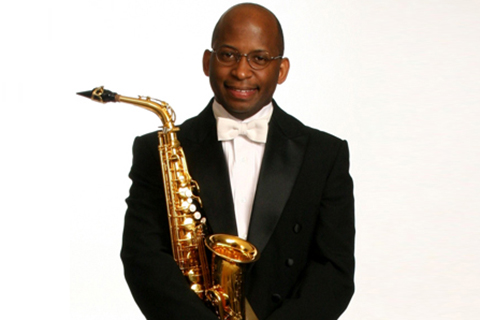 Otis Murphy dressed in a black suit holding a saxophone