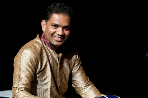 Sam Jeyasingam in a brown jacket