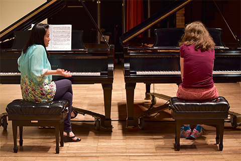 two girls seated at two pianos, side by side