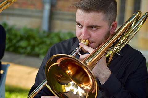 man in a black shirt playing the trombone