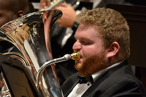 Man in a black suit playing the tuba