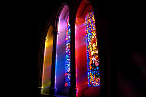 Light filtering in through three colorful stained glass church windows