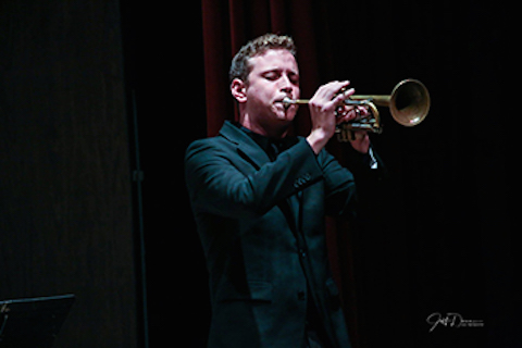 man standing on a dark stage playing a trumpet