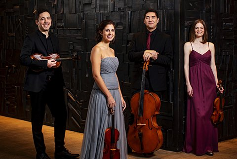 Four formally dressed men and women, posing with string instruments