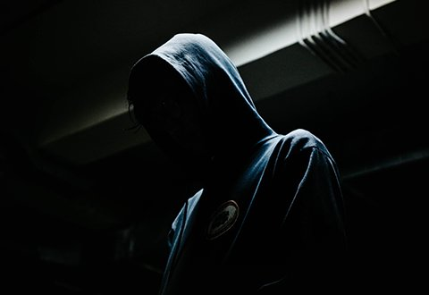hooded person in dark shadow