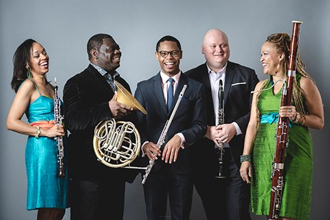 five musicians laughing and posing with wind instruments