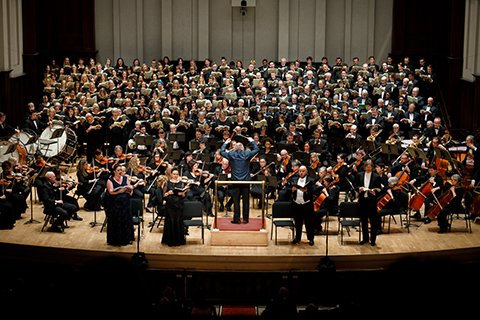 Large symphony orchestra and choir onstage performing