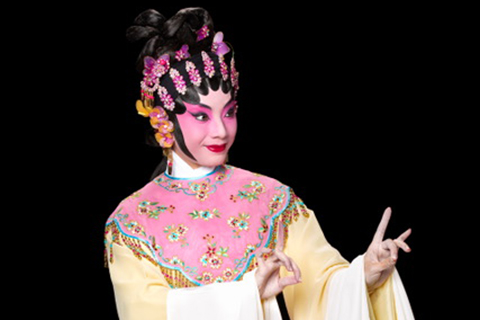 chinese opera performer in pink and yellow robe and pink make up
