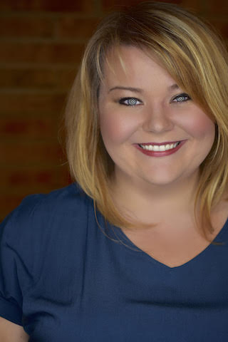 Headshot of Elise Eden in a blue shirt in front of a brick background