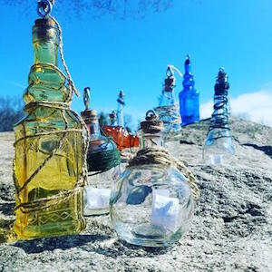 Field art, multi-colored glass bottles, some wrapped with twine, outside on rocks