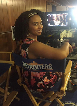 Jillian Mitchell sitting in a directors chair with the word Detroiters on the back