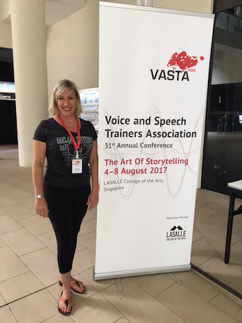 Lynnae Lehfeldt in Singapore at the V A S T A conference, standing next to a banner that says Voice and Speech Trainers Association 31st Annual Conference