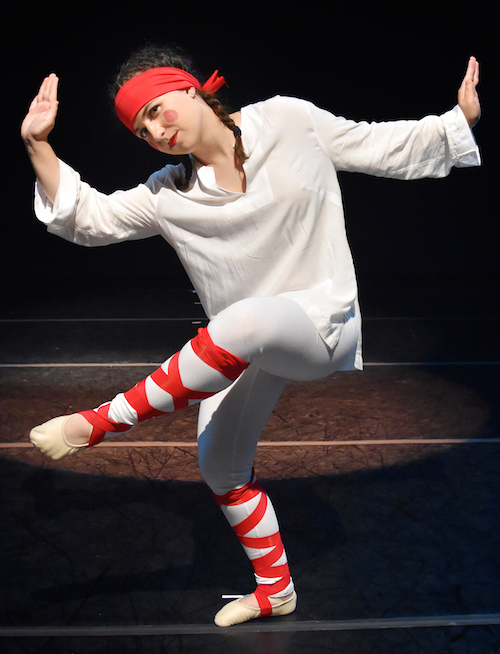 O U dance student performs in The Rite of Spring in a white robe with red headband