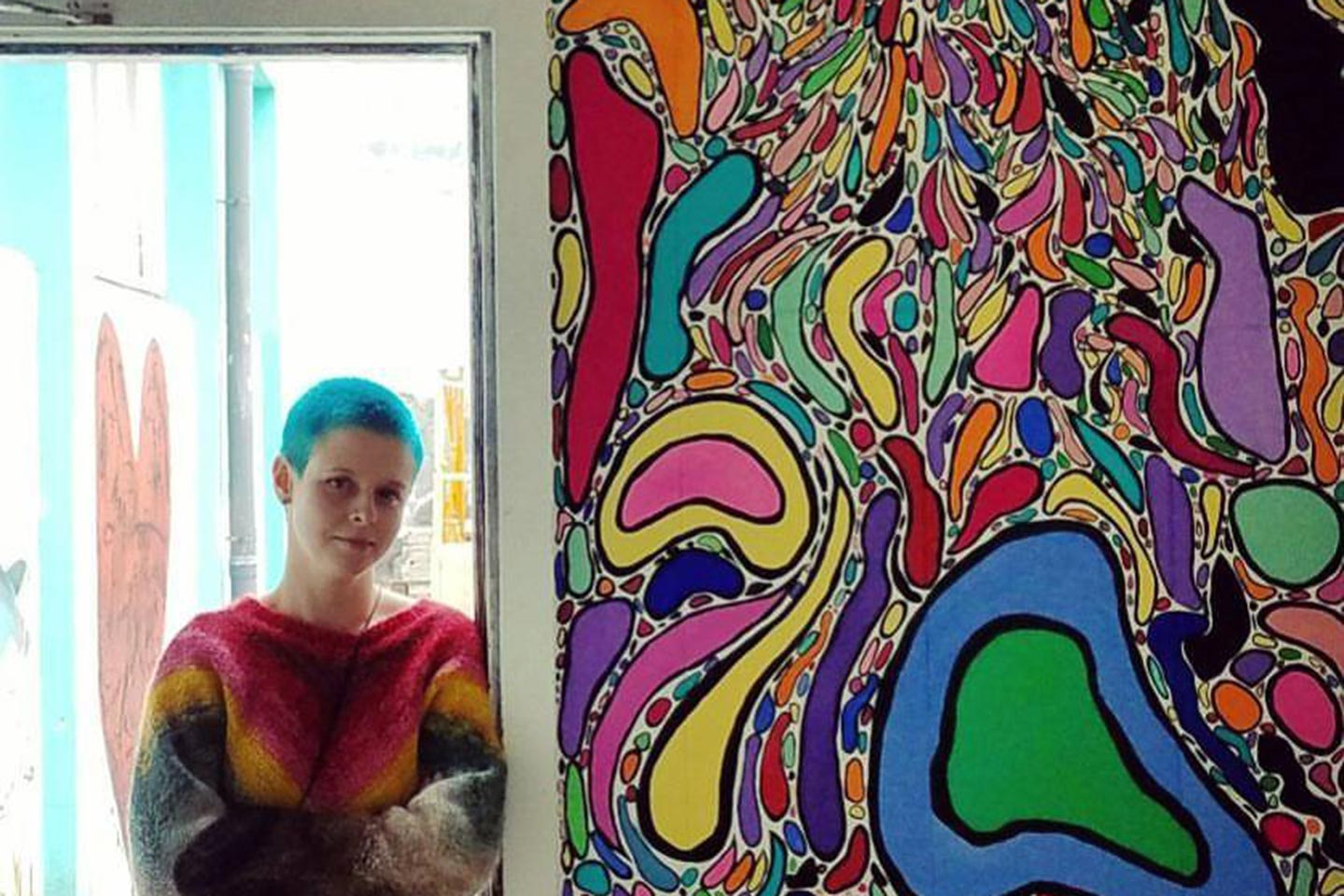 Chelsea Criger standing in an open doorway next to a wall covered in her art work in Iceland