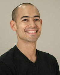 man in a black shirt smiling at the camera