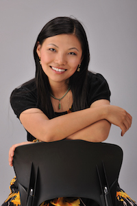 woman in a black shirt, leaning over the back of a chair, smiling at the camera