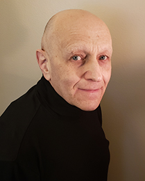 bald man in a black sweater, looking at the camera