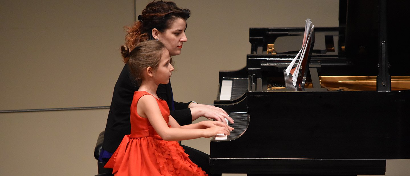 woman and young girl playing a piano together