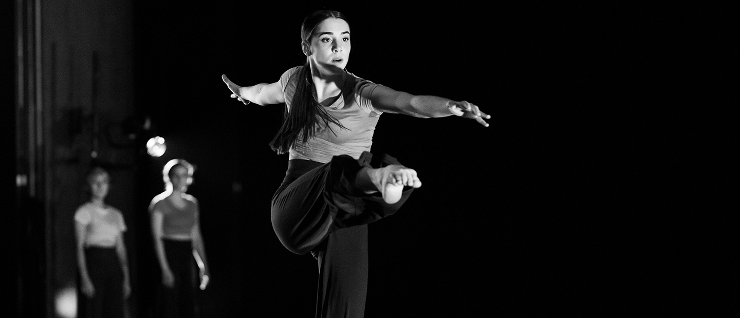 image of a solo female dancer onstage with her leg extended