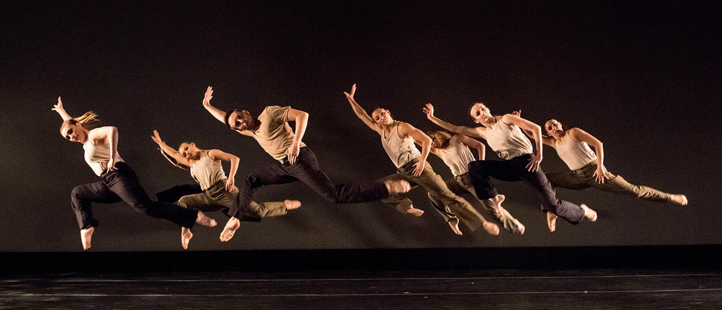 group of dancers leaping into the air, leaning to the right with arms extended