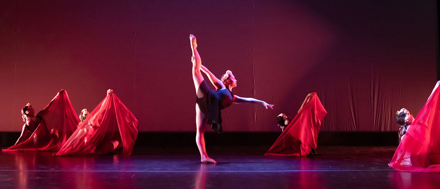 image of one dancer with her leg extended and four dancers in the background