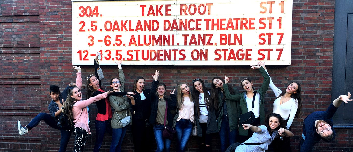 group of students posing beneath a marquee with performances listed on it