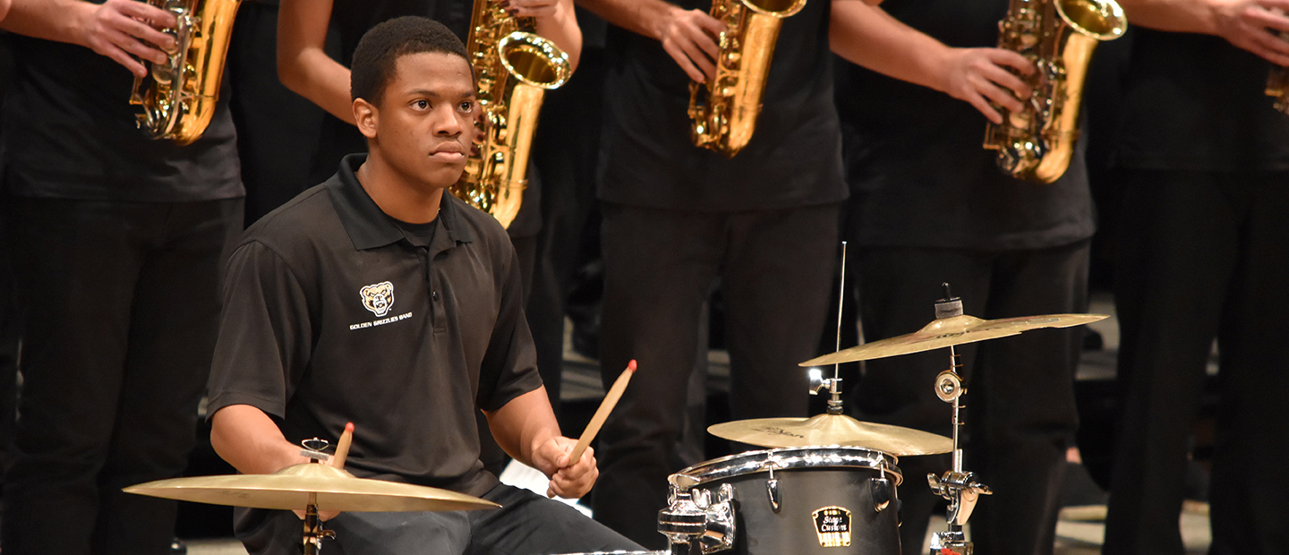image of a young man playing the drum set in an orchestral group