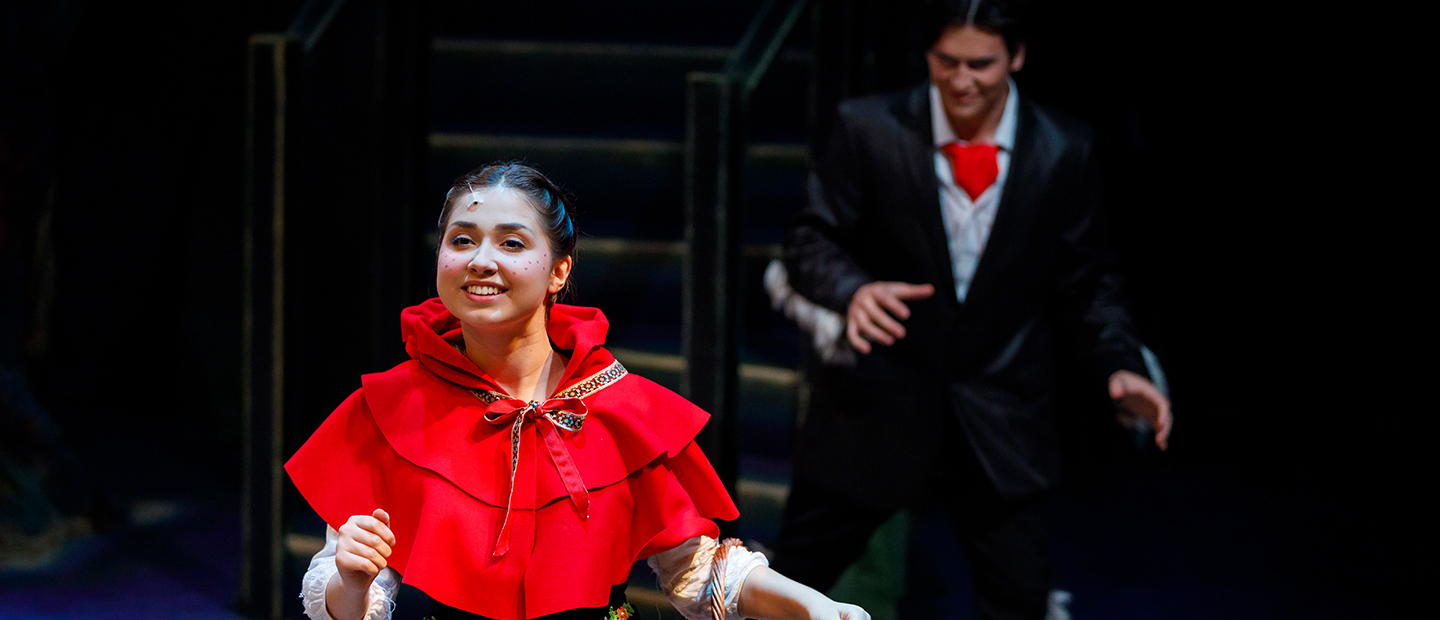 image of a theatre performance, with a girl smiling in forefront and a young man sneaking up behind her