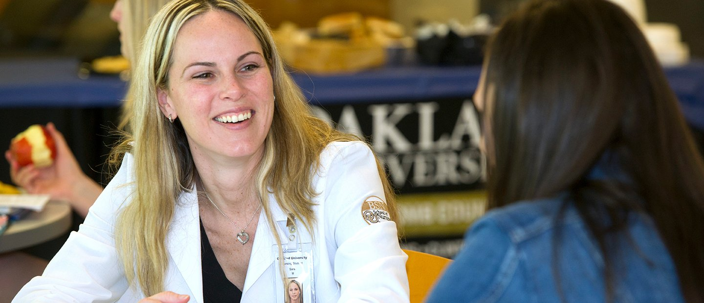 woman in a white lab coat smiling, speaking to another woman in front of her