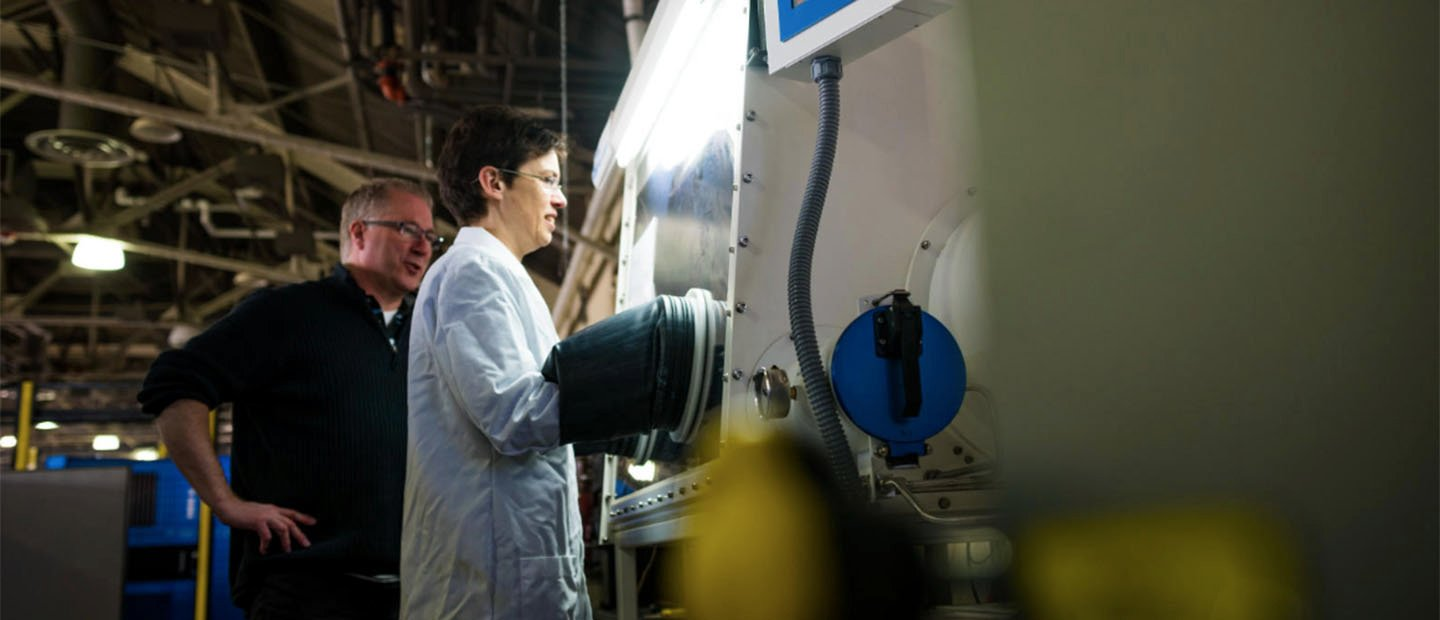 A woman in a white lab coat working at a large machine while a man watches over her shoulder.